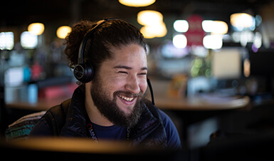 Man with headset smiling and working at a computer